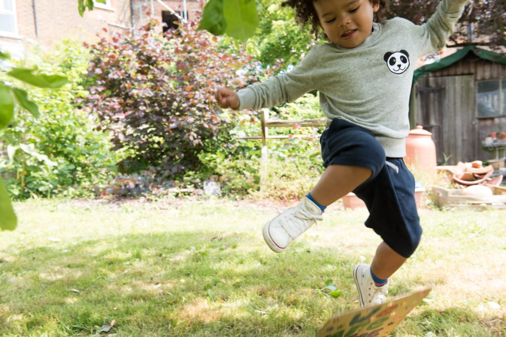 Kid jumping over a chair in Tommy & Lottie jumper at Nurture Collective Ethical Baby Clothing