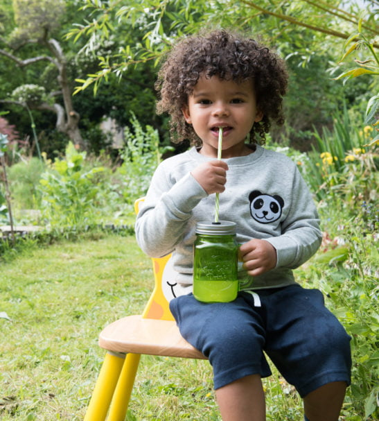 Boy sitting down drinking juice wearing Grey Organic Panda Sweatshirt by Tommy and Lottie and navy blue organic cotton shorts by Cooee