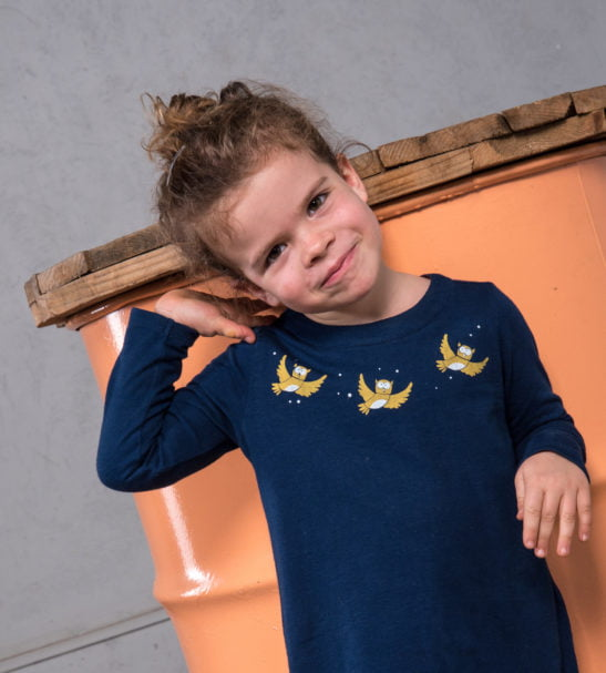 Girl smiling wearing organic Blue Olive Owl Dress with yellow embroidery by Cooee