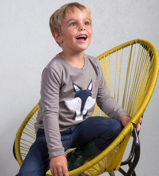 Kid sitting in chair wearing his organic grey Fantastic Mr Fox Sweatshirt with blue and white print by Cooee