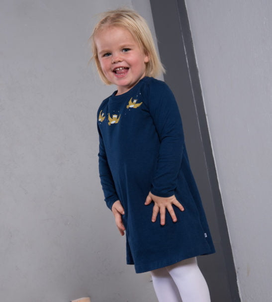 Kid standing in Olive Owl Organic Navy Blue dress with yellow embroidery by Cooee