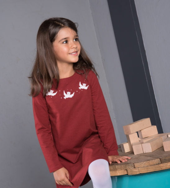 Girl sitting wearing organic Oona Owl Dress in maroon with white embroidery by Cooee