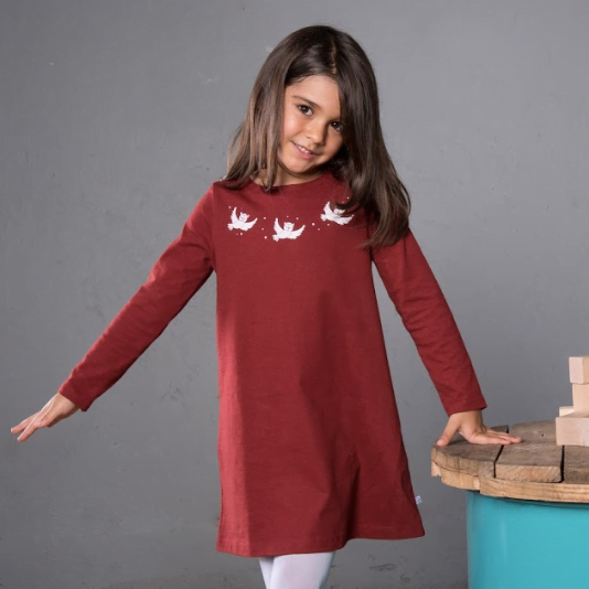 Kid standing wearing Oona Owl organic dress in maroon with white embroidery by Cooee
