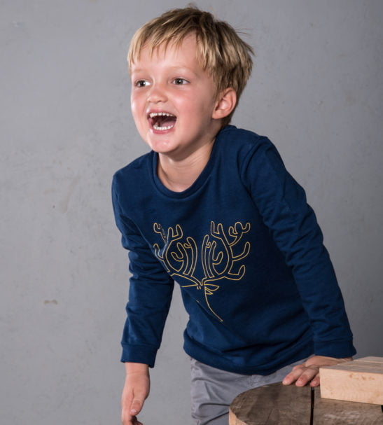 Boy laughing wearing Navy Blue Organic Rue Reindeer Sweatshirt with yellow embroidery by Cooee