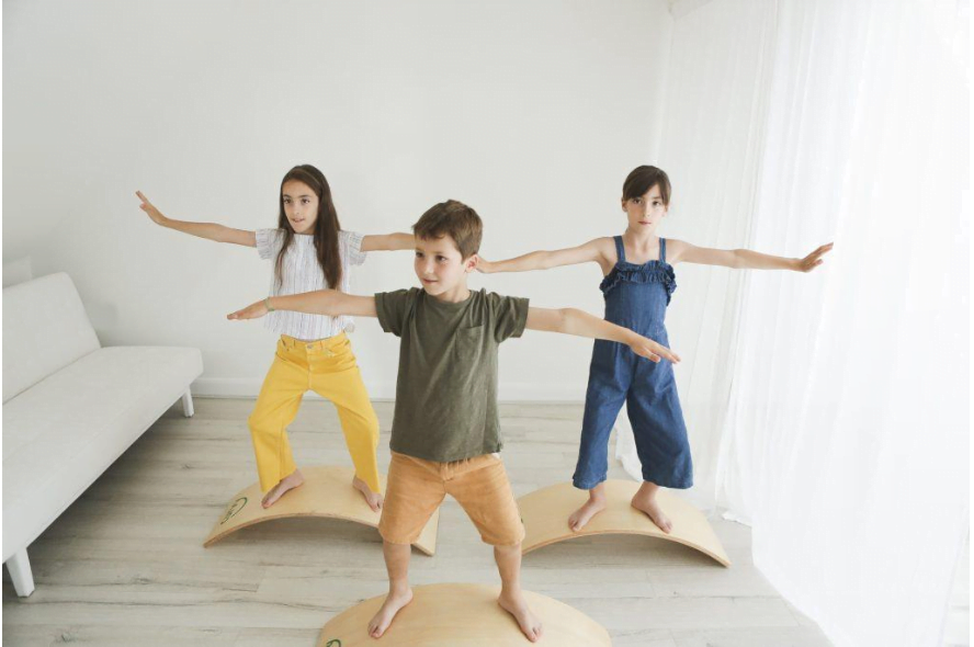 Group of children practicing balancing on a curve board