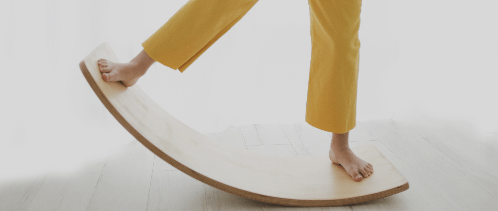 Girl on wooden Curve wobble board Curvy by Young and Learning