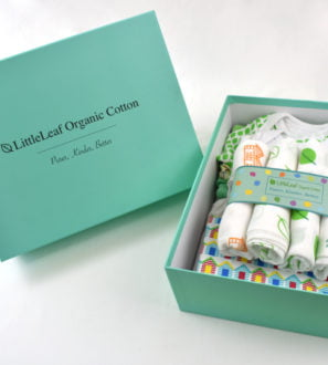 Luxury organic newborn gift box including baby grows, muslins and a baby blanket at Nurture Collective