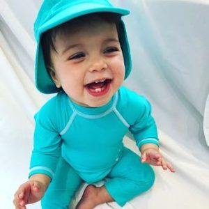 A baby wearing Turquoise All in One Unisex Swimwear by Noma Swimwear at Nurture Collective Ethical Baby Clothing