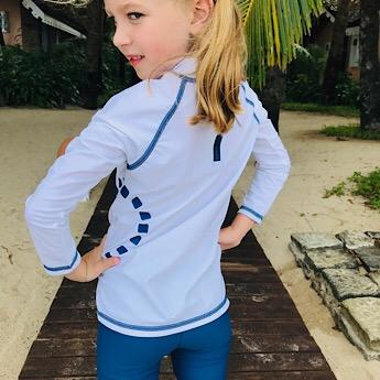 Girl wearing White & Blue Swimwear Top by Noma Swimwear at Nurture Collective Ethical Baby Clothing