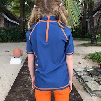 Girl wearing Blue & Orange Short Sleeved Rash Swim Top by Noma Swimwear at Nurture Collective Ethical Baby Clothing