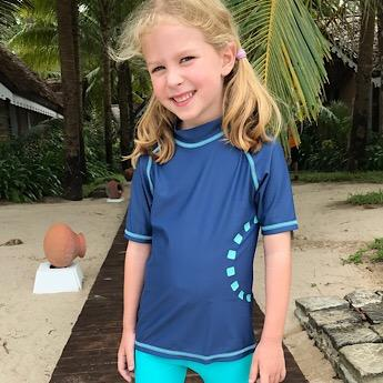 Girl wearing Blue & Turquoise Short Sleeved Rash Swim Top by Noma Swimwear at Nurture Collective Ethical Baby Clothing
