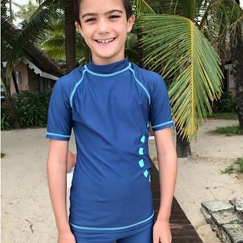 Boy wearing Blue & Turquoise Short Sleeved Rash Swim Top by Noma Swimwear at Nurture Collective Ethical Baby Clothing