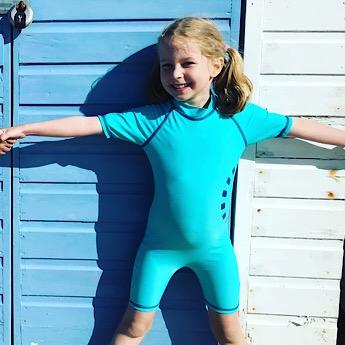 Girl wearing the Children's Turquoise Short Sleeved All in One Unisex Swimwear by Noma Swimwear at Nurture Collective Ethical Baby Clothing