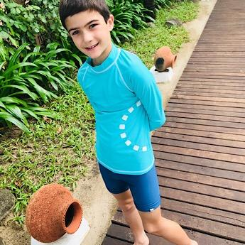 Boy wearing the Unisex Turquoise Swimwear Top by Noma Swimwear at Nurture Collective Ethical Baby Clothing
