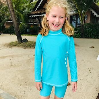 Girl wearing the Unisex Turquoise Swimwear Top by Noma Swimwear Nurture Collective Ethical Baby Clothing