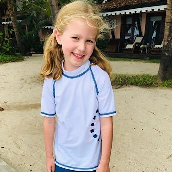 Girl wearing White & Blue Short Sleeved Rash Swim Top by Noma Swimwear at Nurture Collective Ethical Baby Clothing