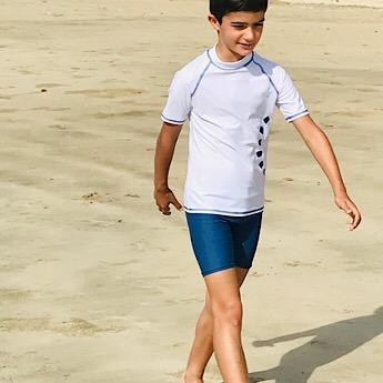 Boy wearing White & Blue Short Sleeved Rash Swim Top by Noma Swimwear at Nurture Collective Ethical Baby Clothing