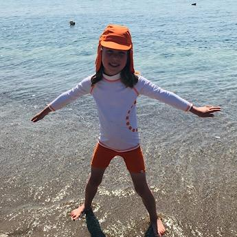 A Girl wearing White & Orange Swimwear at Nurture Collective Ethical Baby Clothing Top by Noma Swimwear