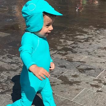A baby wearing a Unisex Turquoise Sun Hat by Noma Swimwear at Nurture Collective Ethical Baby Clothing