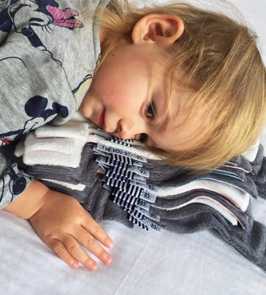 A Toddler Cuddling-Doudoods Baby Comforter stack at Nurture Collective Ethical Baby Clothing