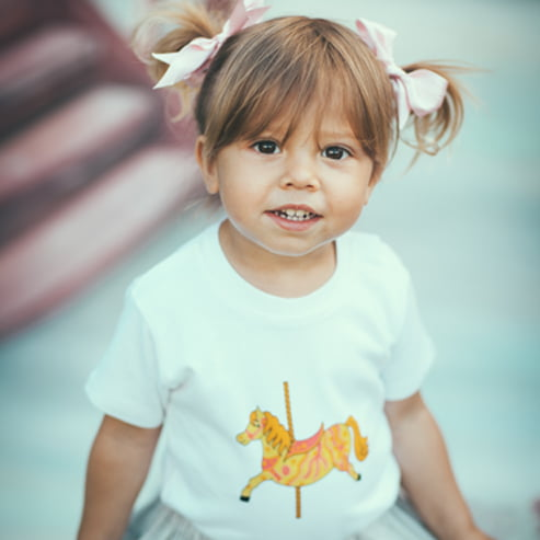 Little Girl wearing the Carousel Short Sleeved T-Shirt by Tommy & Lottie at Nurture Collective