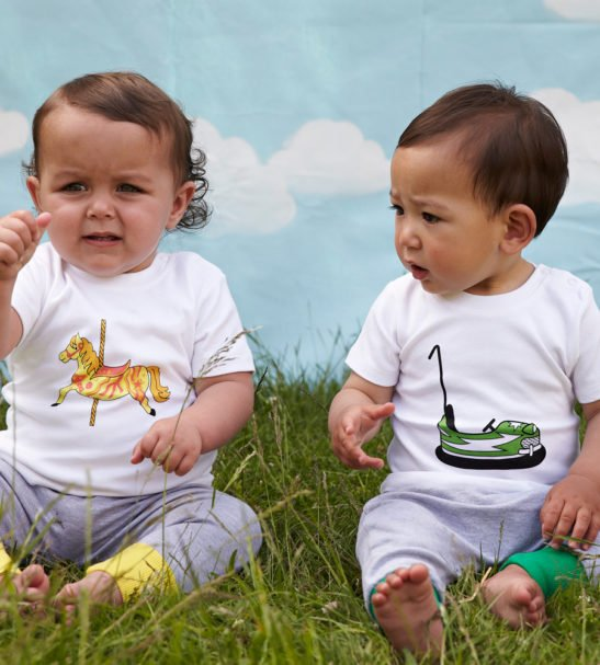 Two babies wearing the wearing the Carousel & Dodgem Short Sleeved T-Shirt with Yellow & Green Harem Pants by Tommy & Lottie at Nurture Collective