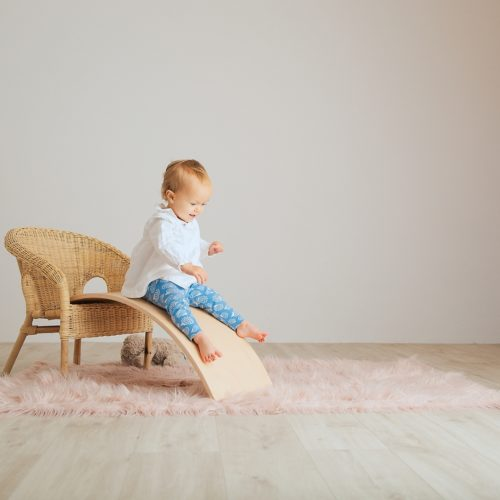 Child sliding down a Wooden Balance Board by Young & Learning at Nurture Collective