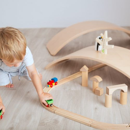 Child Playing with the Wooden Balance Board Making Railway Tracks by Young & Learning at Nurture Collective
