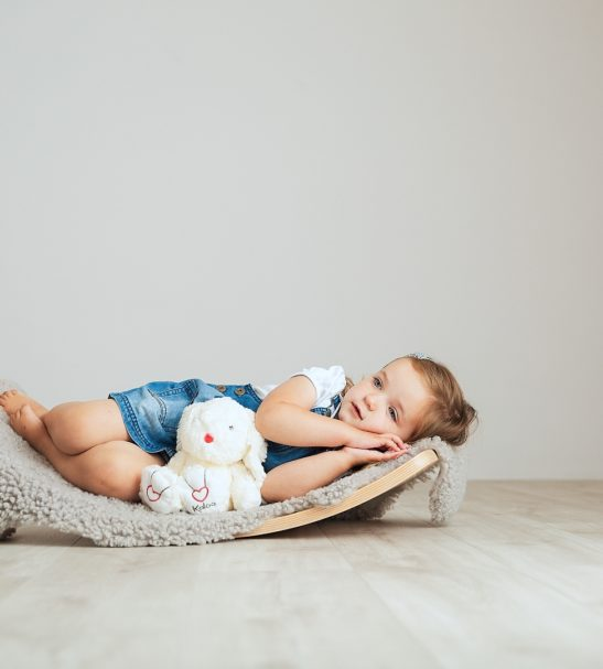 A Child Lying Rocking on a Wooden Balance Board by Young & Learning at Nurture Collective