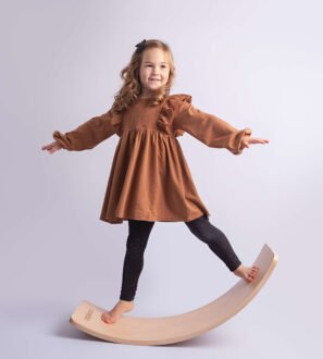Curvy wooden Balance Boards by Capikooa Adventurer size Little girl standing rocking on the the Waldorf inspired wooden balance board