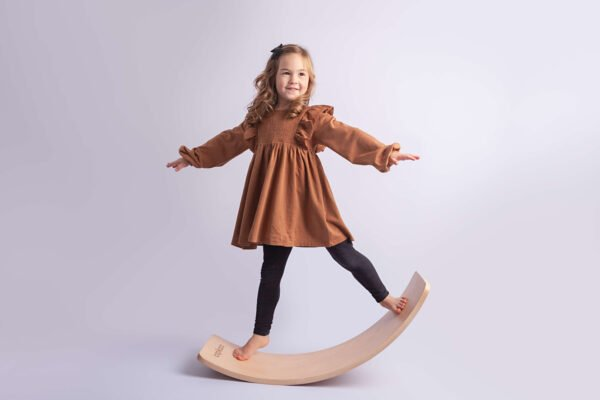 Capikooa Adventurer size Little girl standing rocking on the the Waldorf inspired wooden balance board