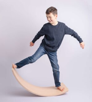 Boy rockinging on Capikooa Pioneer sized Waldorf inspired wooden balance board