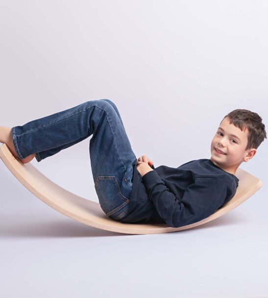 Curvy wooden Balance Boards by Capikooa Pioneer size with one kid sitting on the wooden balance board
