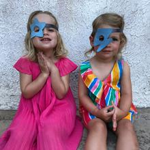 Two toddlers wearing their blue star and flash eye patches.
