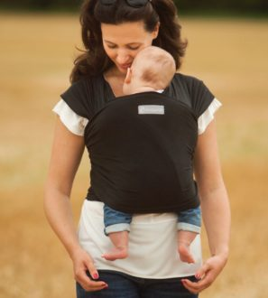 Mum carrying a baby in a Black Sling at Nurture Collective