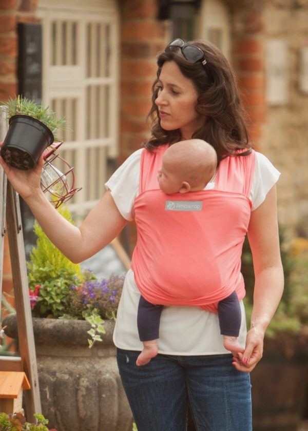 Mum carrying a baby in a Coral Pink Baby Sling at Nurture Collective