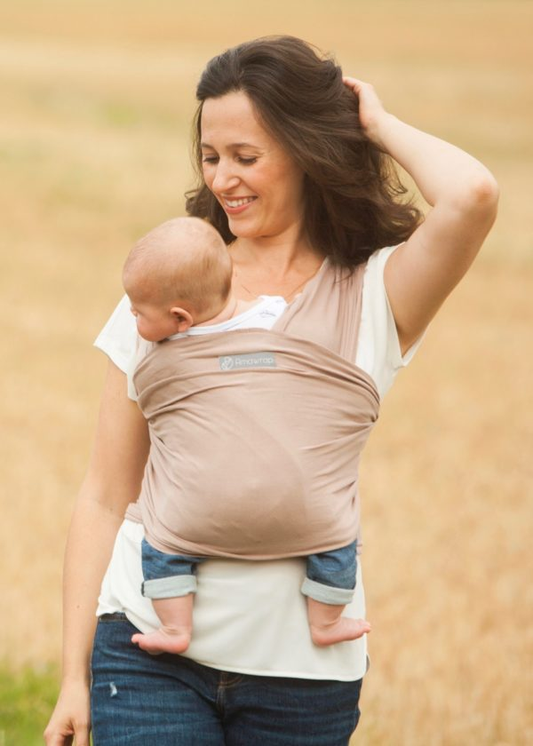 Mum carrying a baby in a Mocha Cream Baby Sling at Nurture Collective