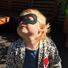A toddler is comfortable wearing the super-soft Kids Bandit Mask for halloween at Nurture Collective.