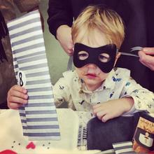 A mum getting the toddler ready with a Kids Bandit mask which is perfect for a superhero halloween costume at Nurture Collective.