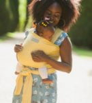 Mum carrying a baby in a Mustard_Yellow Baby Sling at Nurture Collective