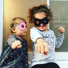 Two children wearing a Kids Bandit mask ideal for superhero halloween costumes at Nurture Collective.
