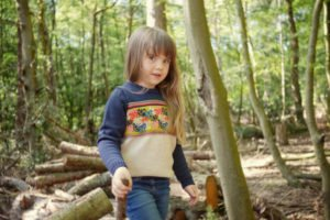 Little Girl Wearing Merino Forest Pattern Jumper by Faraway Gang at Nurture Collective