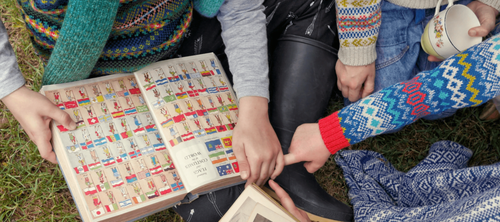 Little Boy & Girls Wearing Jumper's and reading a Book by Faraway Gang at Nurture Collective