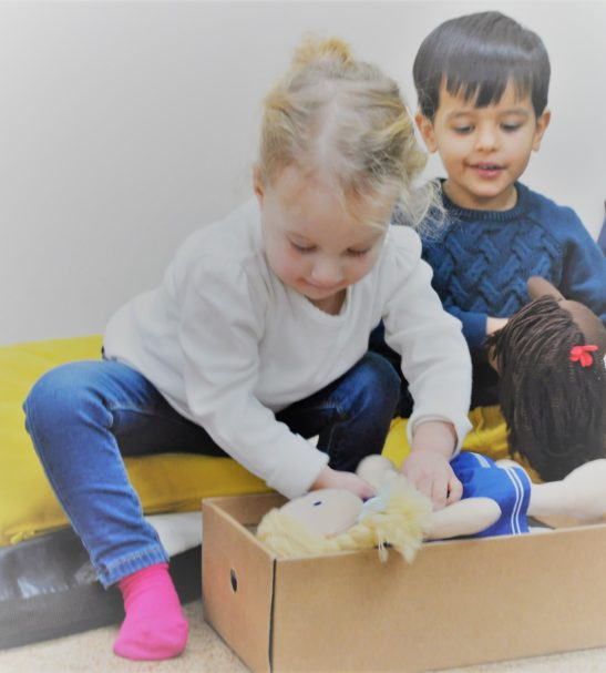 A Girl Putting Lively Lea Soft Doll by Dear One World into a Box at Nurture Collective