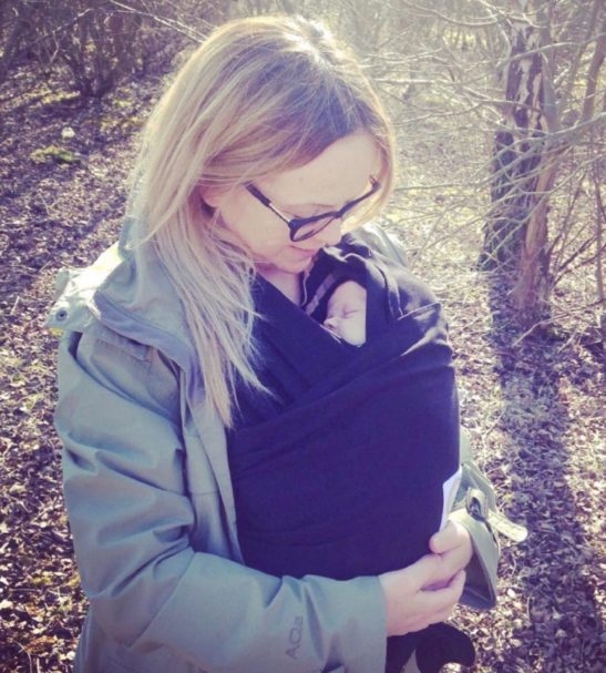 Mum wearing a Raven Black Baby Carrier by Amawrap at Nurture Collective