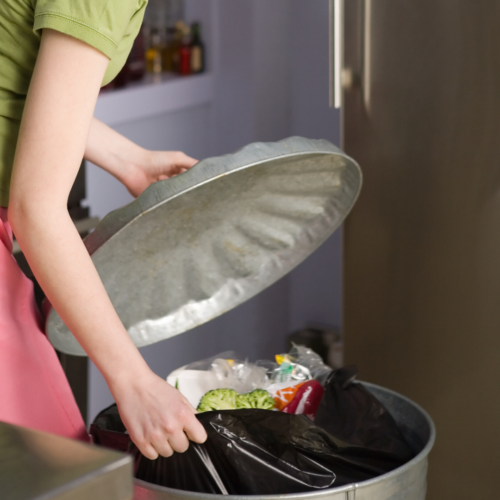 A Woman putting rubbish in her bin at Home Part of Nurture Collectives Sustainable Blog