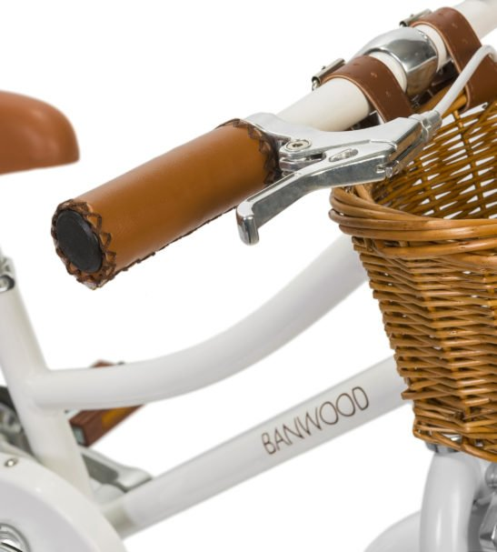 Close up of a Banwood Classic White Pedal Bike with a basket & Bell perfect a for childs first bike now available at Nurture Collective