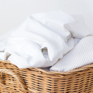 plie of white sheets for washing in a basket for the Nurture Collective blog