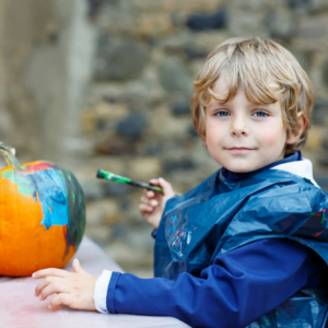 Boy painting a pumpkin in his painting overalls for a Nurture Collective blog