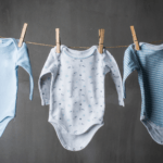 Babygrows on a washing line for the eco friendly sustainable nursery swaps blog at Nurture Collective